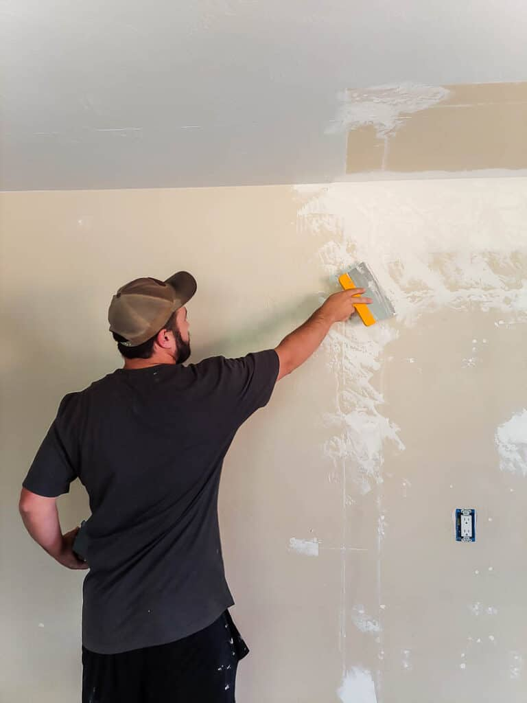 man applying trowel texture at the middle of the wall