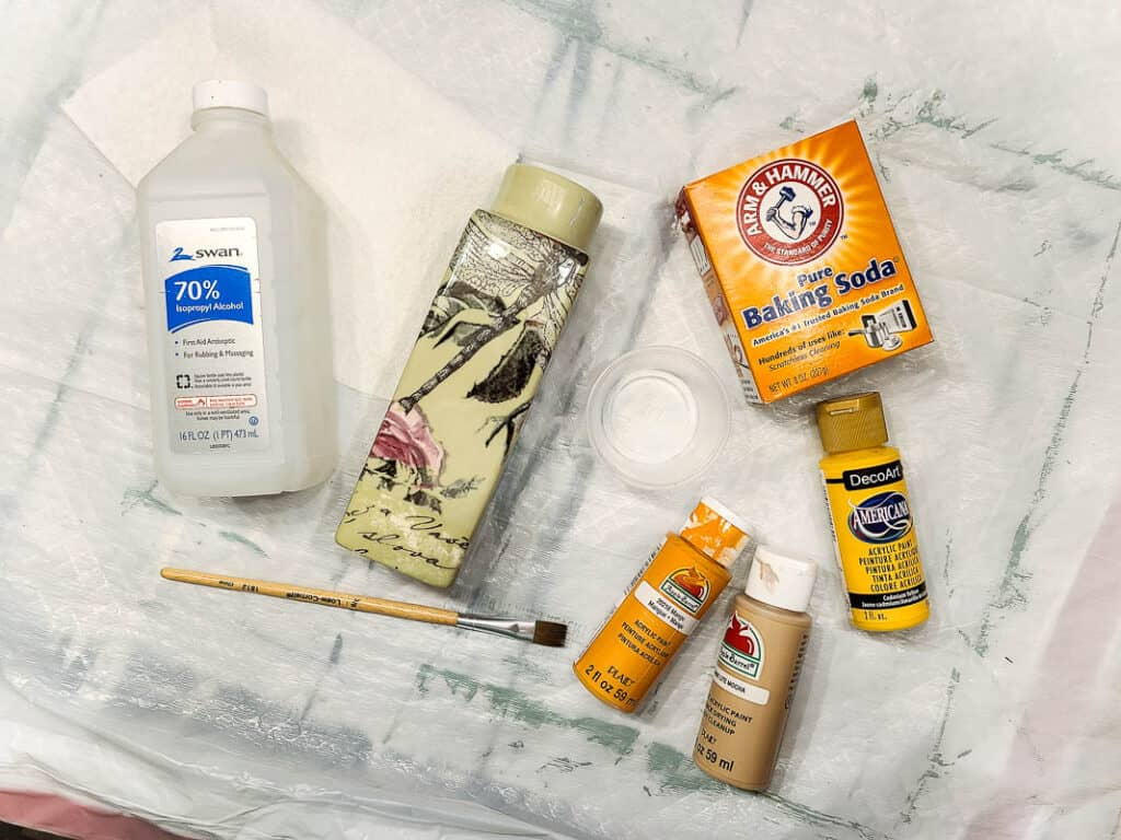 Bottle of alcohol, floral vase, paint brush, cup, box of baking soda and three bottle of paint