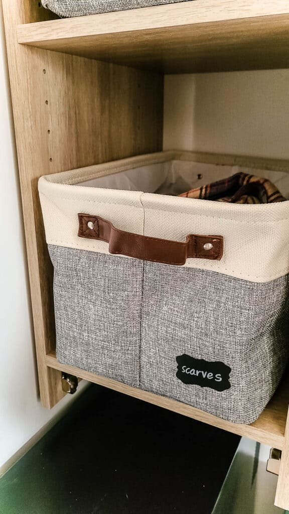 Tan and gray basket with leather handle with chalk board label that says scarves on a shelf in a closet