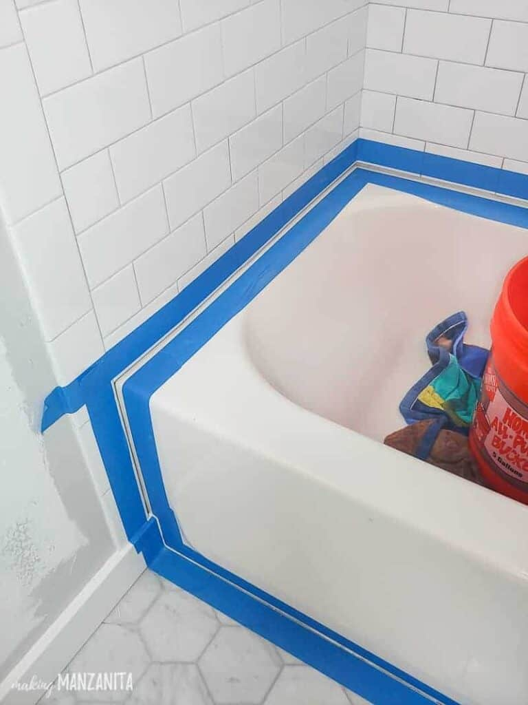 Painter's tape all over the edges of the bathtub before getting caulked and white subway bathroom tiles up to the bathroom floor