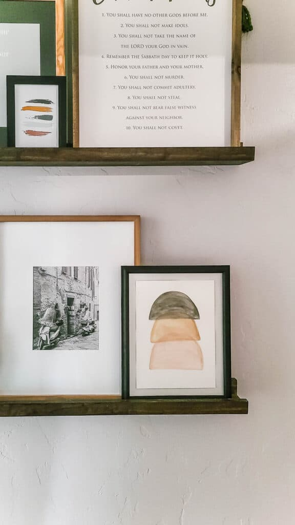 neutral boho wall art watercolored with stacked semi circles on shelves beside a photo frame