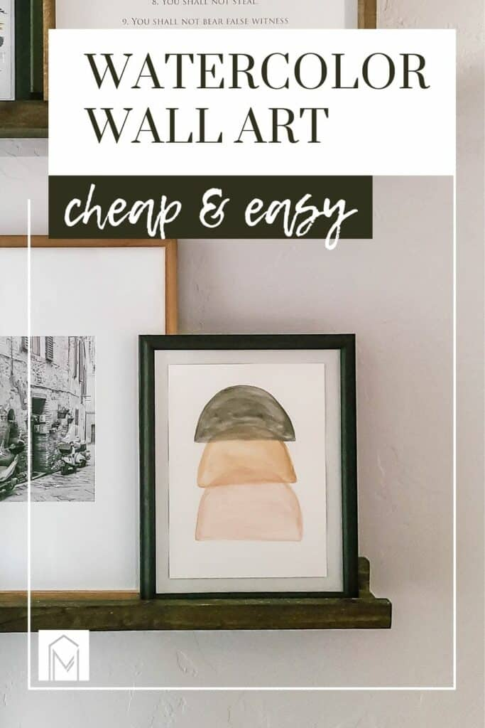 Stacked semi circle abstract watercolor painting in black frame on floating ledge shelf with text overlay that says watercolor wall art cheap & easy