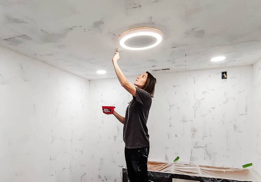 Woman holding a paint brush and red cup and preparing the ceiling before painting it with roller