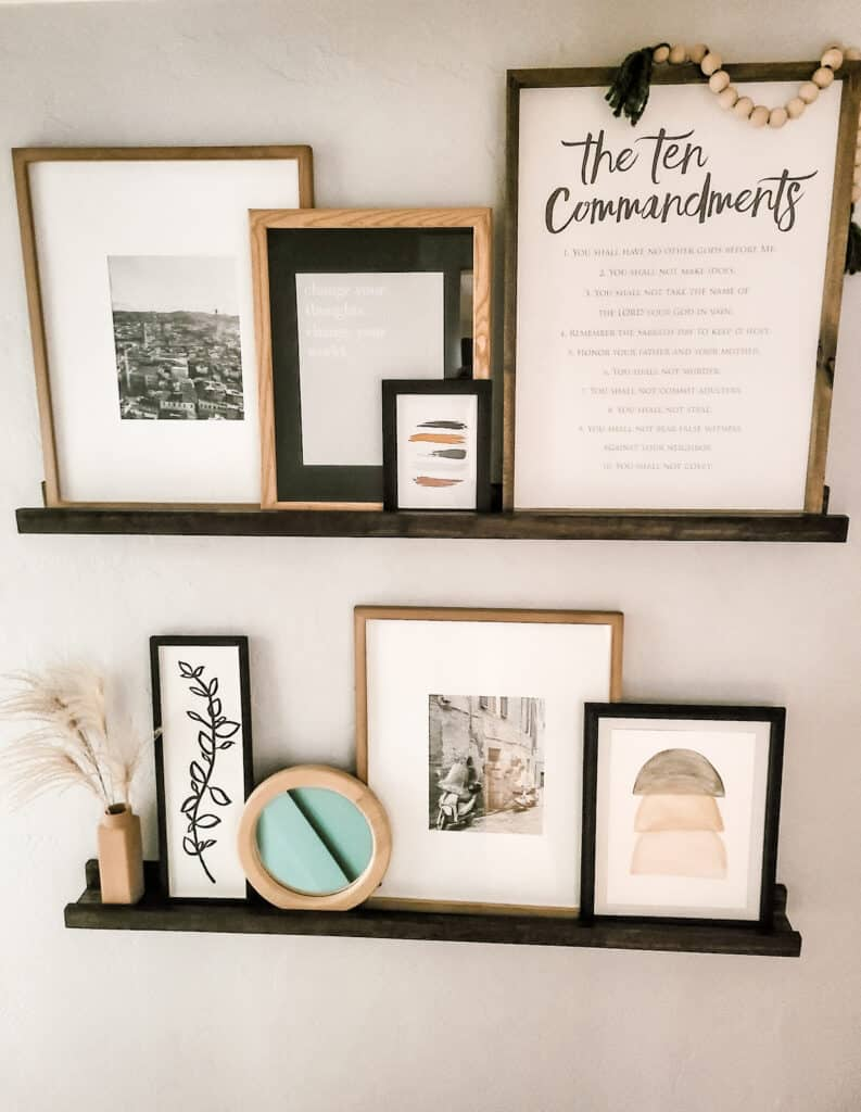 Prints and photos arranged on picture ledge shelves in hallway