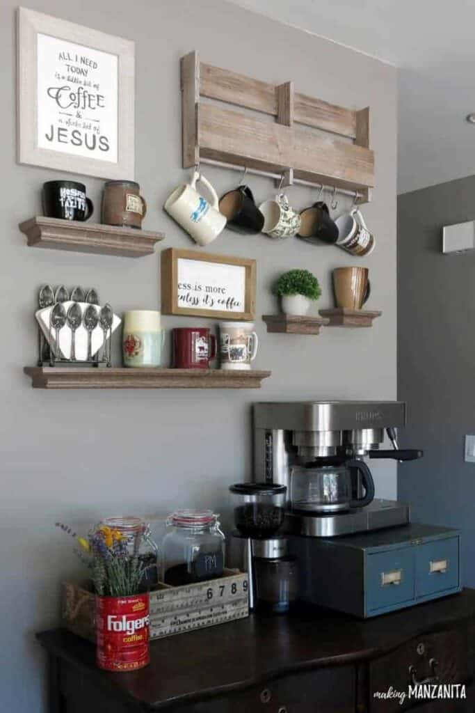 Gray wall painted with Behr Fashion Gray in home coffee station with hanging mugs and shelves on wall and a coffee machine on top of a farmhouse style drawer and coffee grounds canisters beside