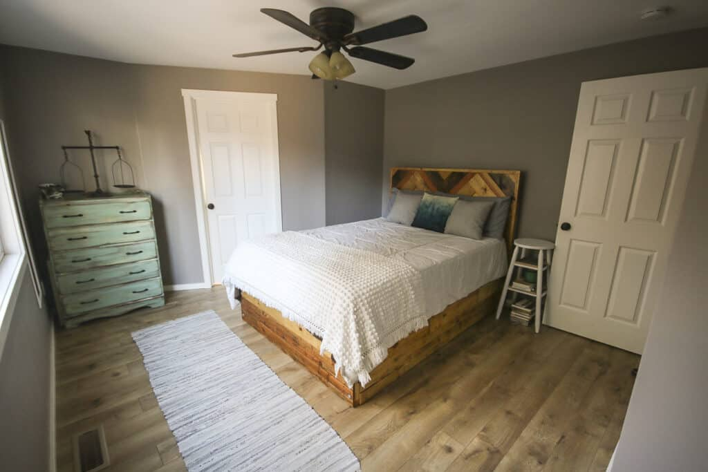 Master bedroom side view of the bed, rug, wooden side table and a farmhouse drawer with decor on top beside the bathroom white door and a ceiling fan with chandelier and a painted wall with fashion Gray by Behr