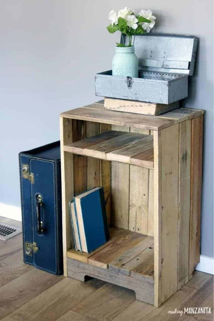 Pallet side table with books and topped with a painted mason jar with fake flowers, chest and a book beside a vintage blue suitcase all leaning in the gray painted wall