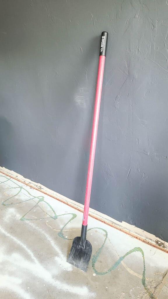 floor scraper standing against gray wall