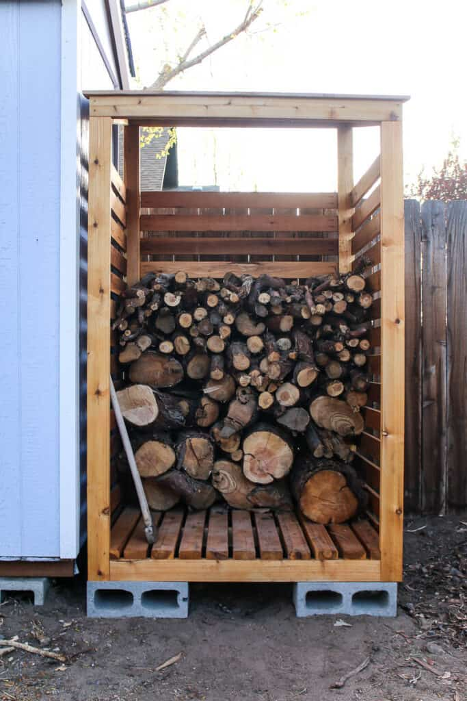 Front full view of the DIY firewood storage rack with pile of fire wood stacked neatly inside