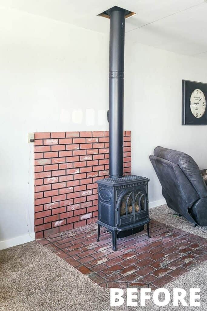 Black gas freestanding fireplace on the brick wall behind that goes half way up the wall and floor behind the gray recliner
