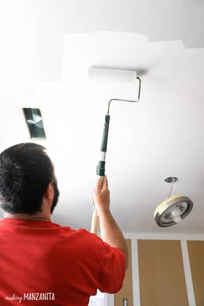 Man wearing red shirt holding a roller and painting the ceiling with white paint
