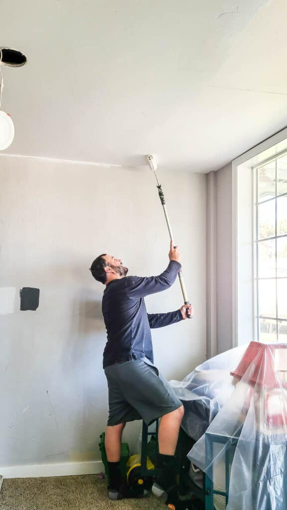 Man standing in front of the furniture covered in plastic and holding a roller painting the ceiling