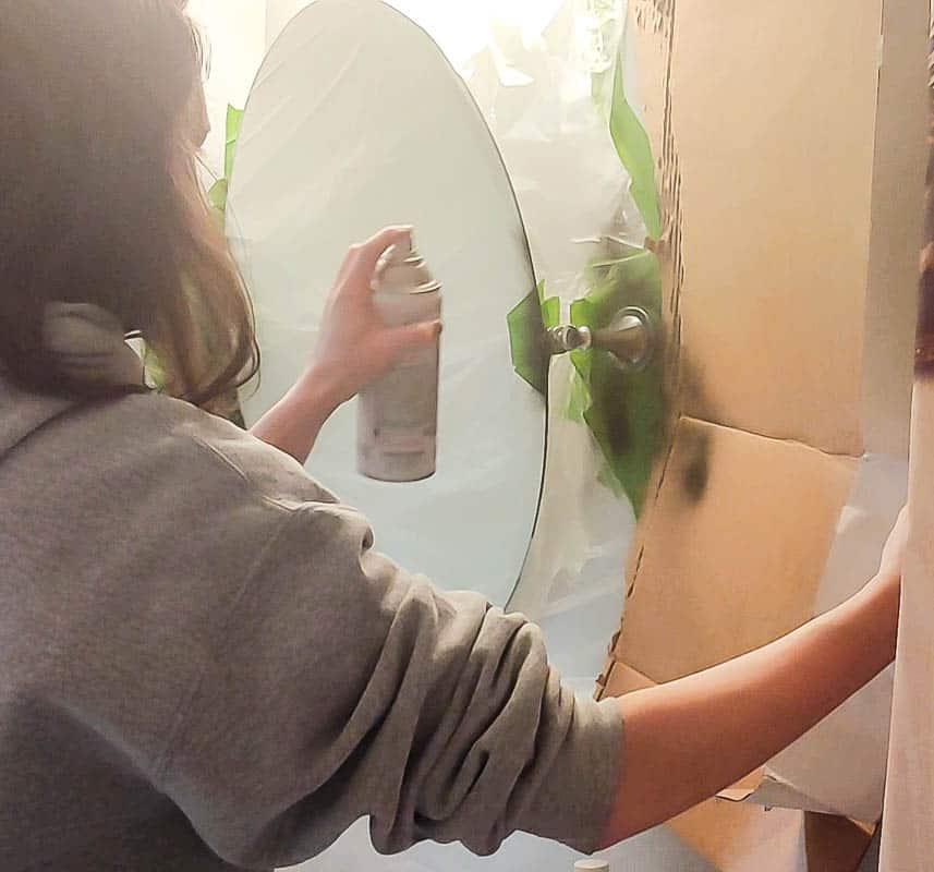 Woman spray painting the mirror handle black
