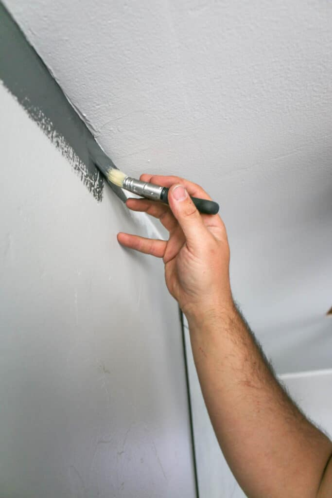 Man holding an angeled paint brush painting the ceiling edge with a straight line with gray paint without using painter's tape
