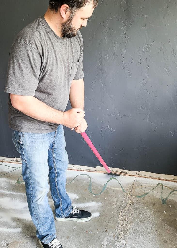 man using floor scraper to remove tack strip