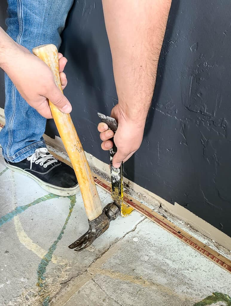 removing tack strip from concrete with hammer and pry bar