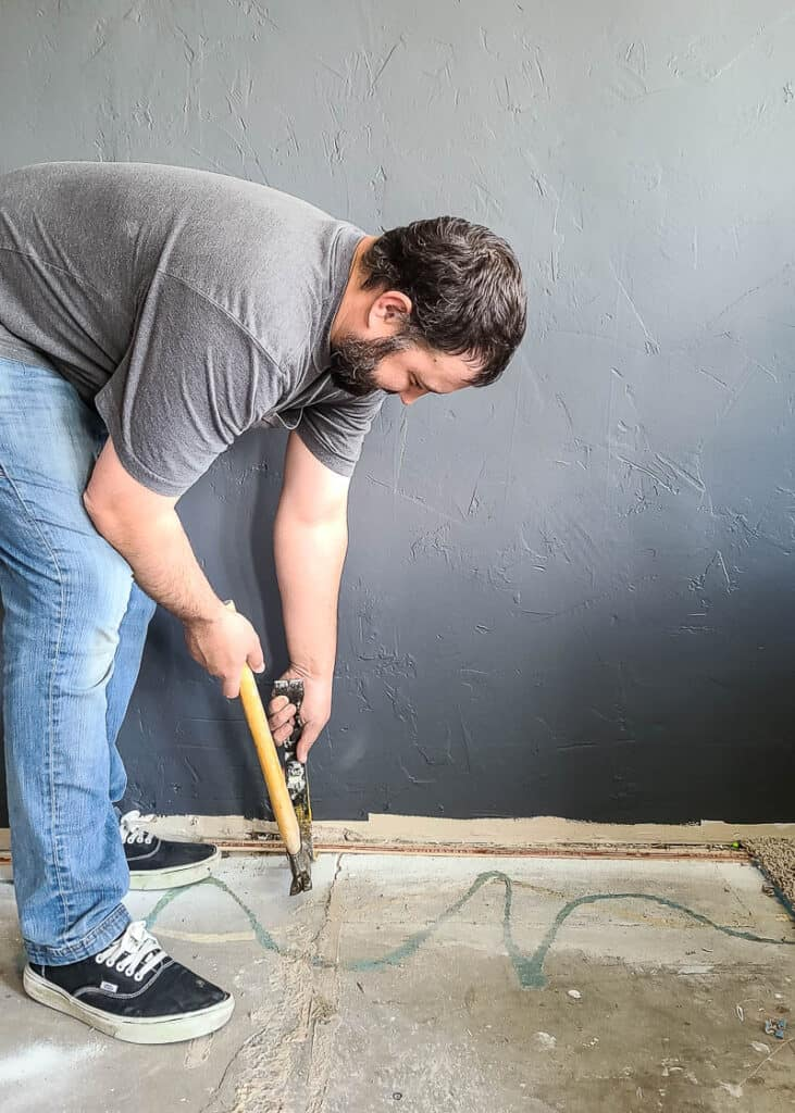 man using hammer and pry bar to remove tack strip