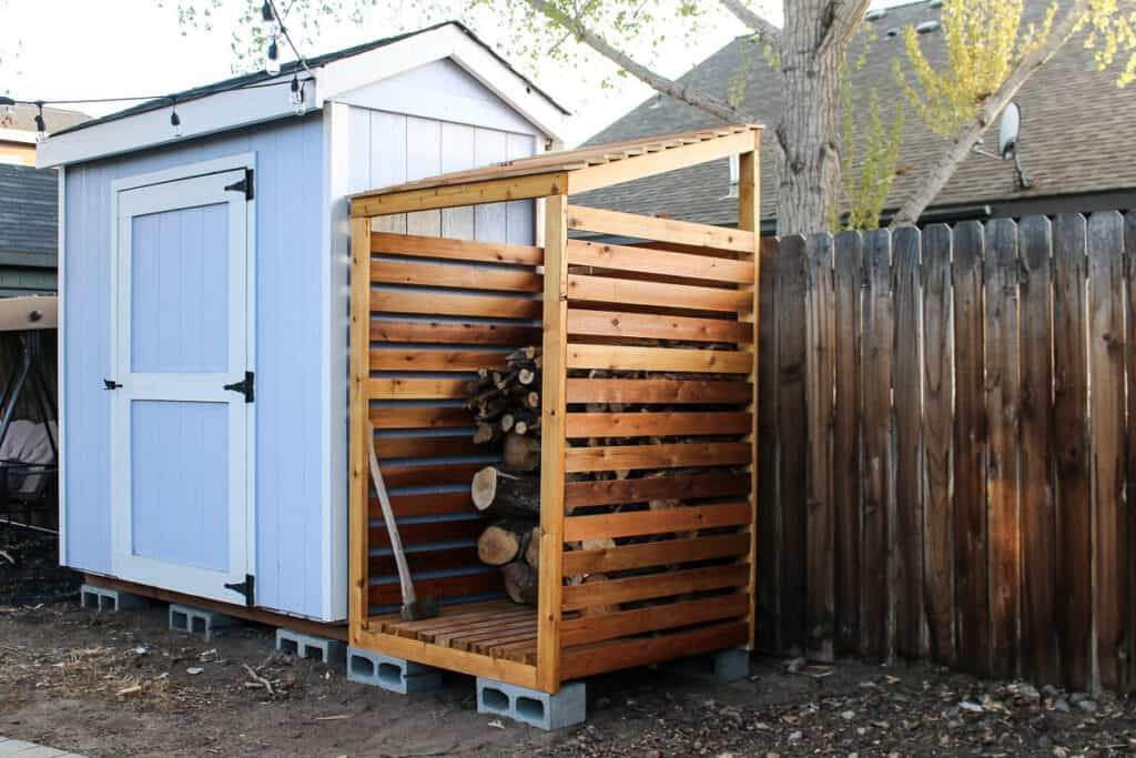 DIY firewood rack in the backyard beside the garden shed and wooden fence