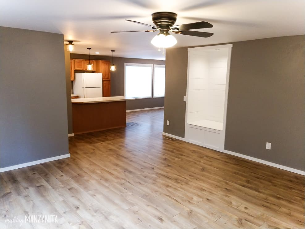 Gray paint walls throughout the living room, kitchen and dining room with laminate floors, white window and trim and industrial chandeliers