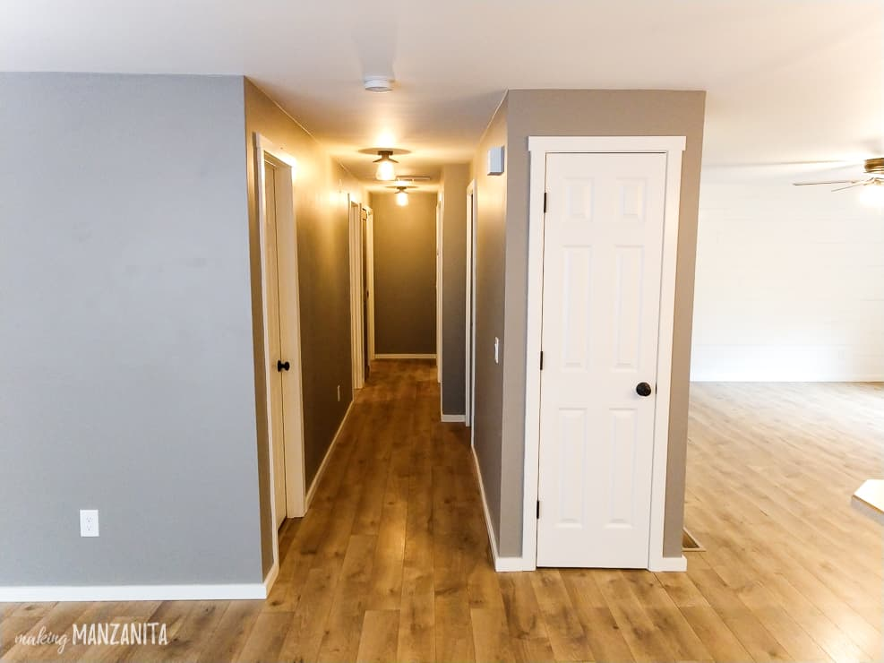 Long hallway with Fashion gray paint and white doors and trim