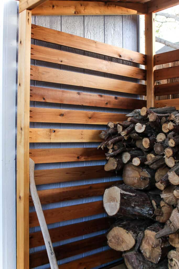 Close up view of the do it yourself cedar firewood rack with pile of fire wood inside stacked up