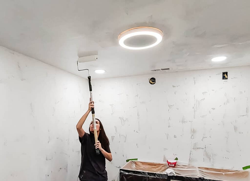 Woman in black shirt holding a paint roller and painting the ceiling while standing beside the plastic covered furniture