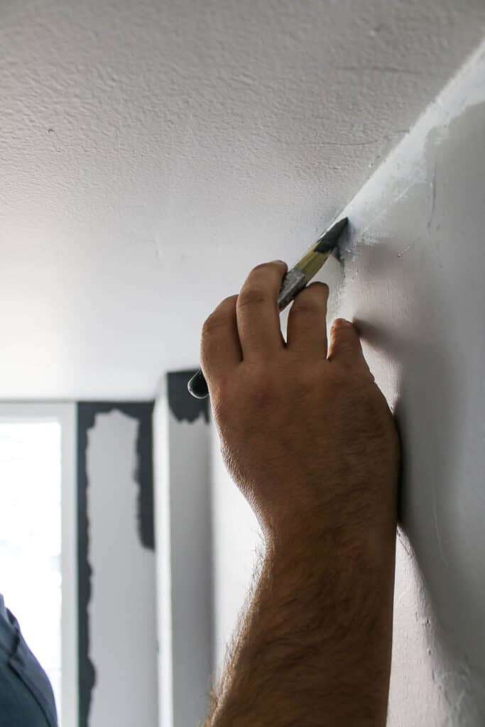 Hand holding an angeled paint brush with a steady hand cutting in paint on the wall with gray paint where the wall pieces the ceiling corner