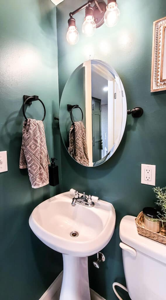 Newly painted matte black vanity mirror, dark green painted walls, towel holder, black wall mounted soap bottle, small bathroom sink and light fixtures after the update