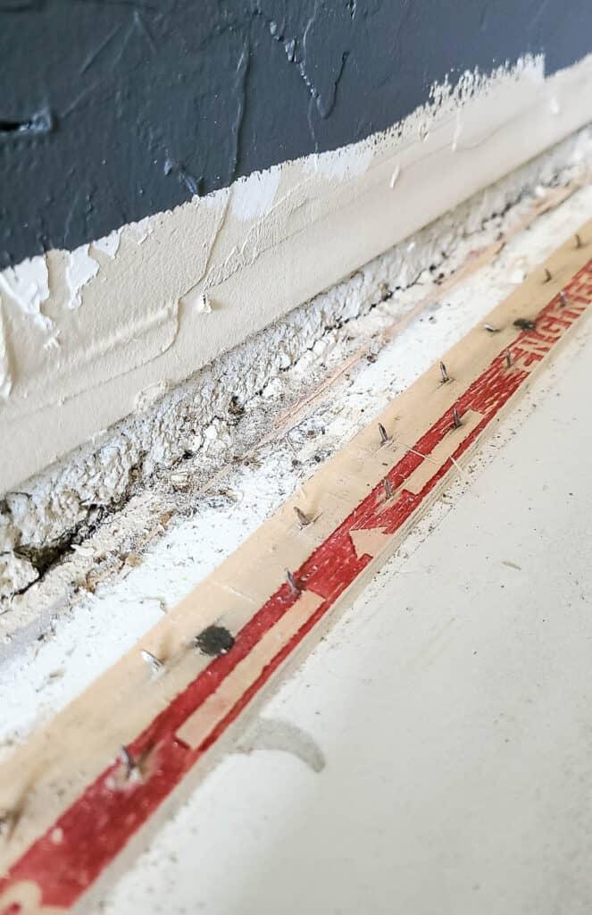 carpet tack strip along perimeter of wall