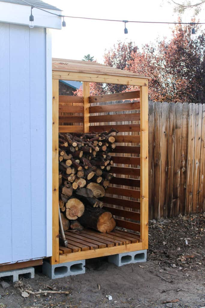 Side view of the DIY firewood rack with pile of firewood inside