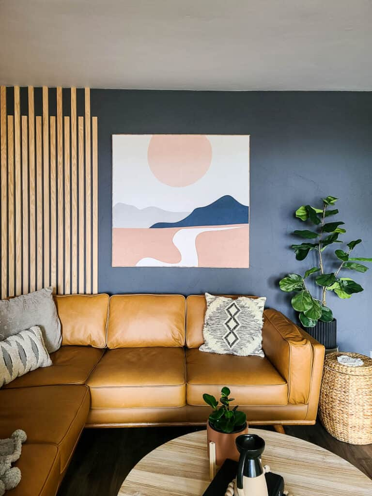 Full view of fabric wall art using society6 tapestry with mountains and sunset in the modern boho living room hanging on the wall beside wood accent wall above the article leather sectional and boho throw pillows