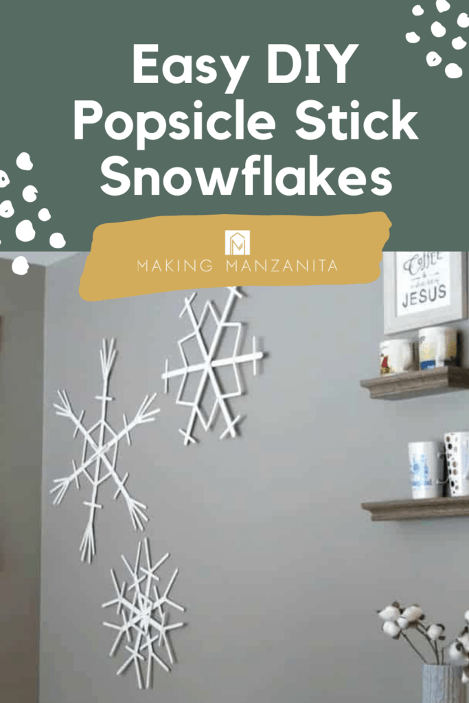 Popsicle stick snowflakes hanging on the wall in the winter designed dining area with text overlay that says Easy DIY popsicle stick snowflakes