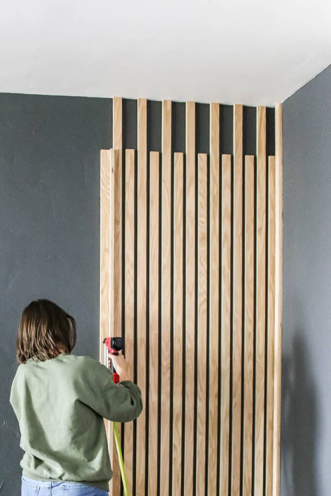 Front view of the wood slats attached to the wall and woman attaching vertical wood slats using a brad nailer
