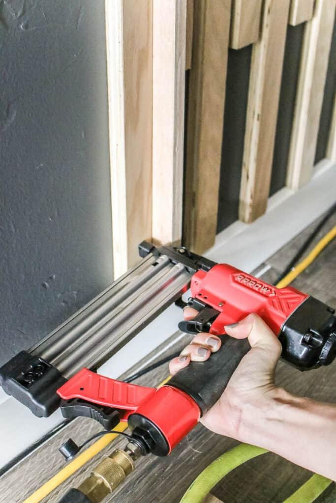 Woman nailing the wood slat in the wall using brad nailer