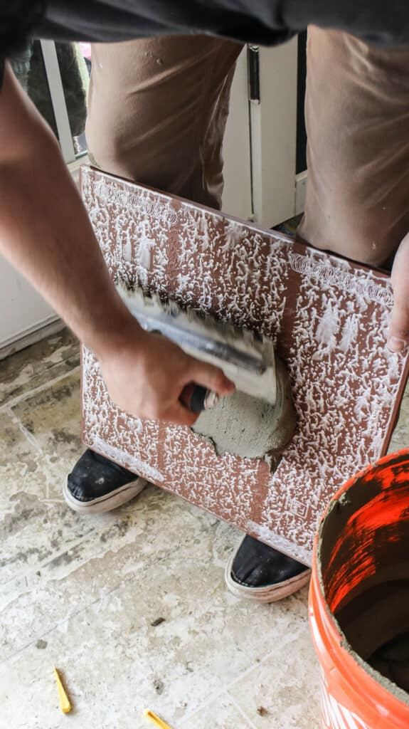 Man applying mortar at the back of the tile with the back butter technique