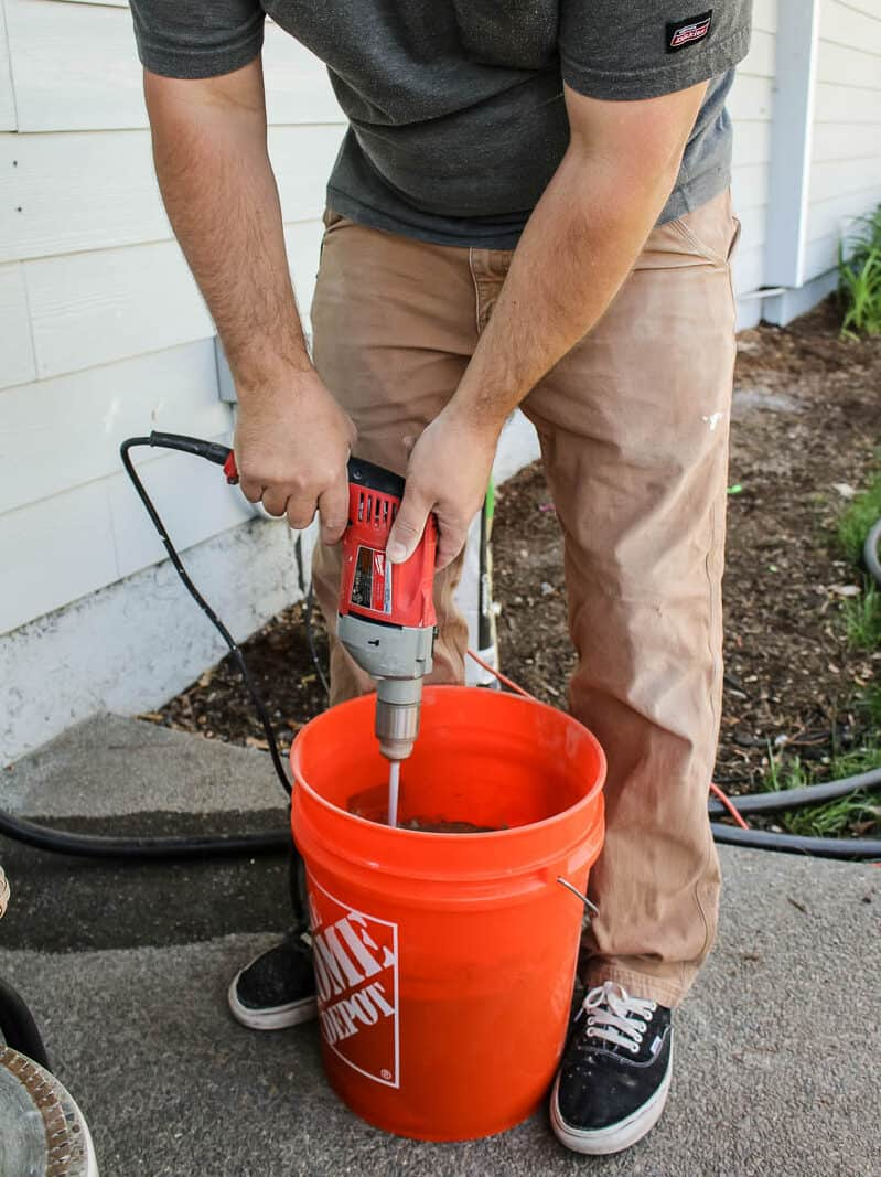 Man holding a corded drill mixing the thinset and water mixture inside the orange bucket
