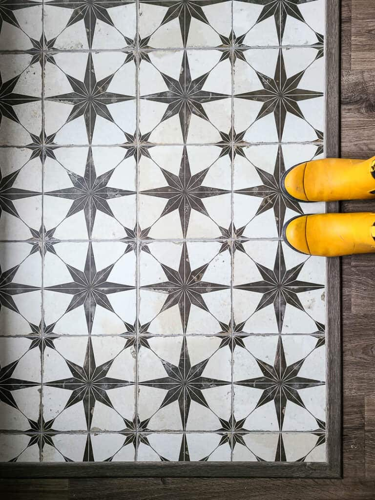 Ivory and brown star pattern Floor tiles laid on the floor in entryway with yellow boots on the side