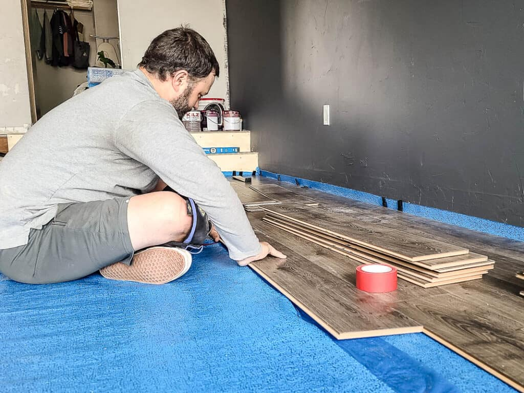 Man sitting on the floor attaching laminate floors on top of underlayment with pile of laminate and tape