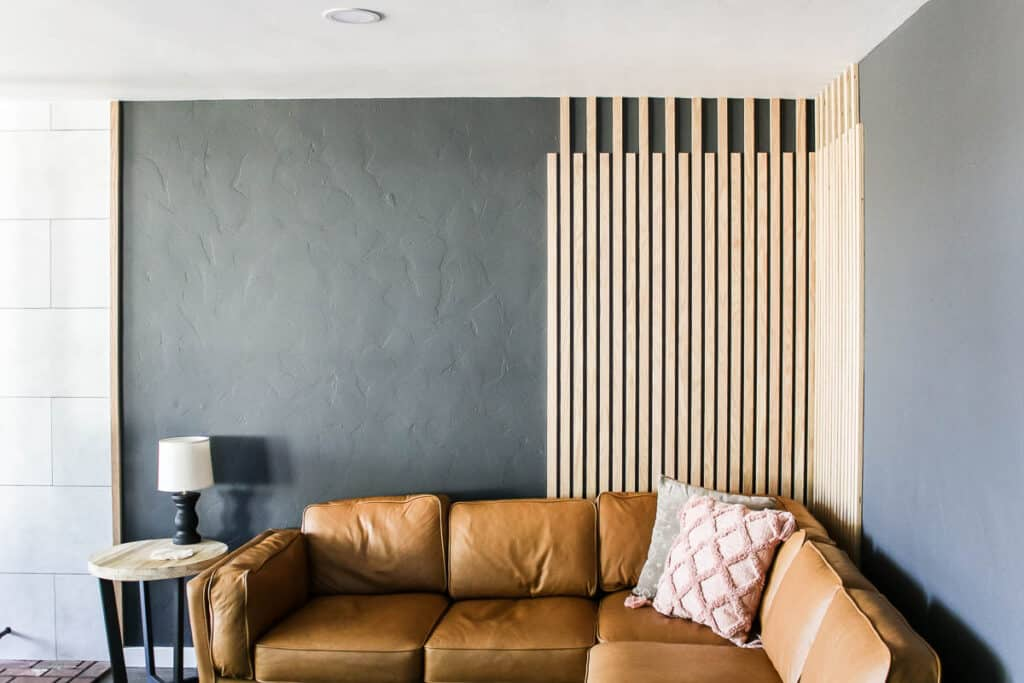 DIY Slat Wall as Wood Accent Wall in the living room with wood side table, lamp, leather couch and throw pillows