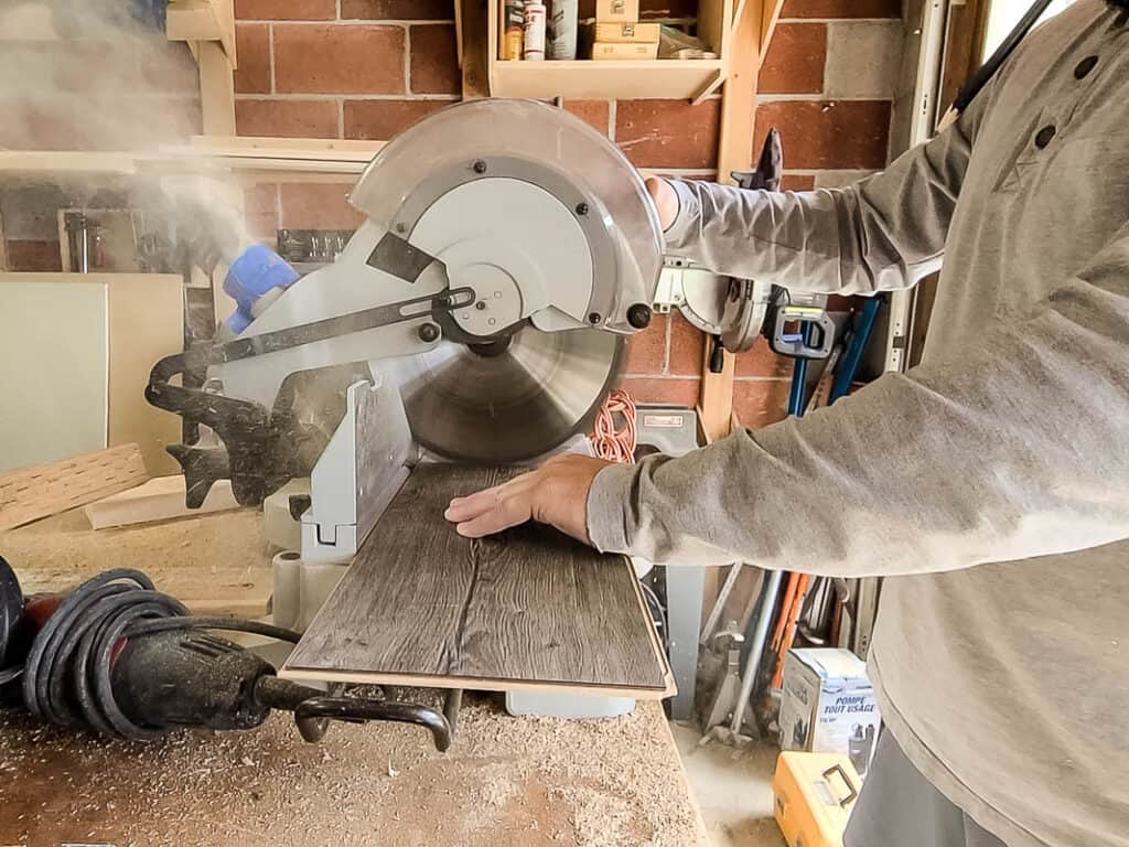 Man cutting the laminate using a miter saw on the table workbench