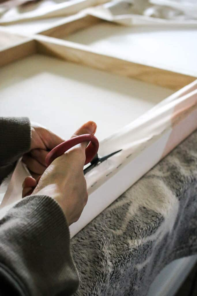 Woman cutting the excess tapestry on the back of canvas using scissors