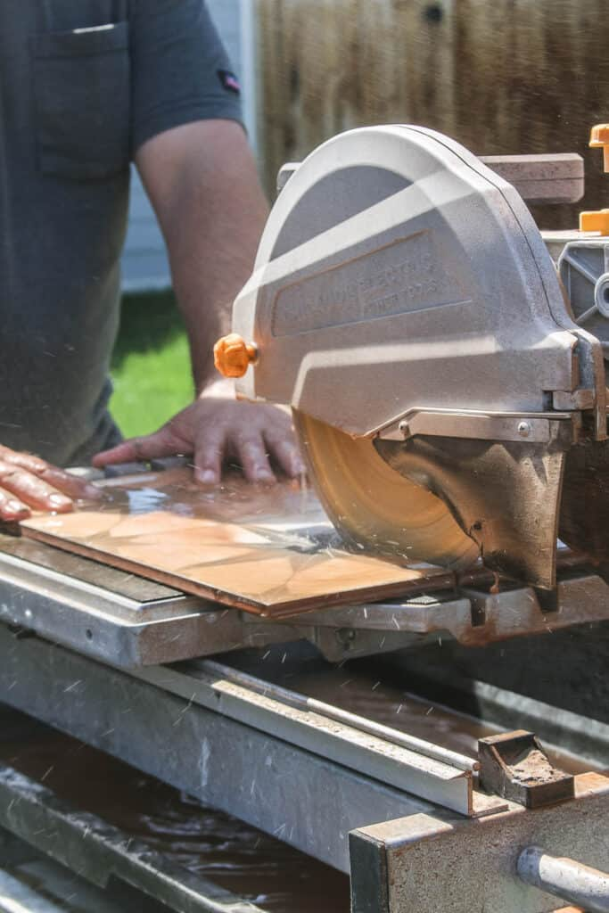 Man cutting floor tile with wet tile saw