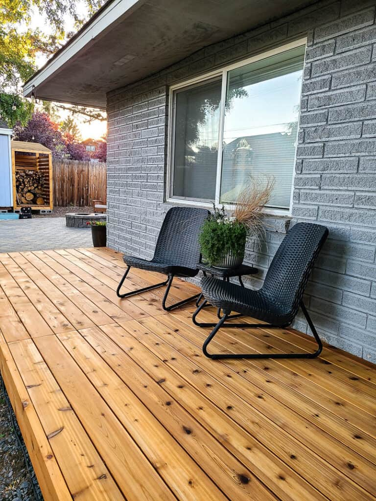 Side view of the backyard with wood deck and black chairs, center table and plants as decor