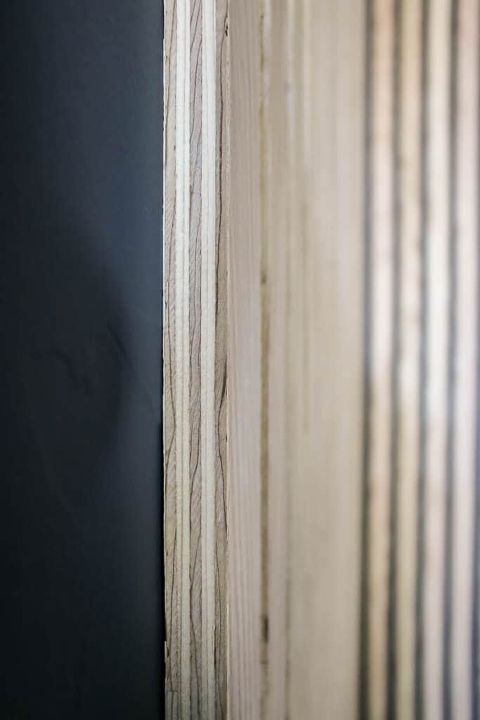 Close up of slat of wood nailed to the wall with plywood edge exposed