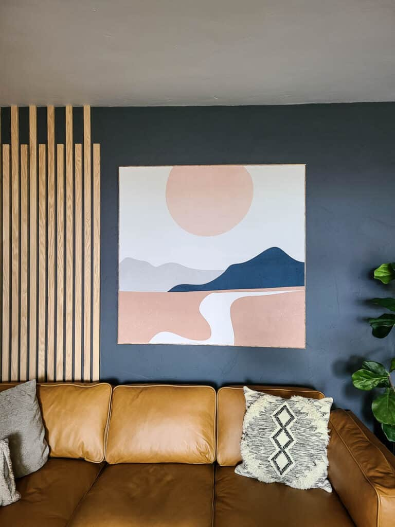 Fabric wall art on the living room hanging on the wall beside wood slat wall above the tan leather couch and boho throw pillows