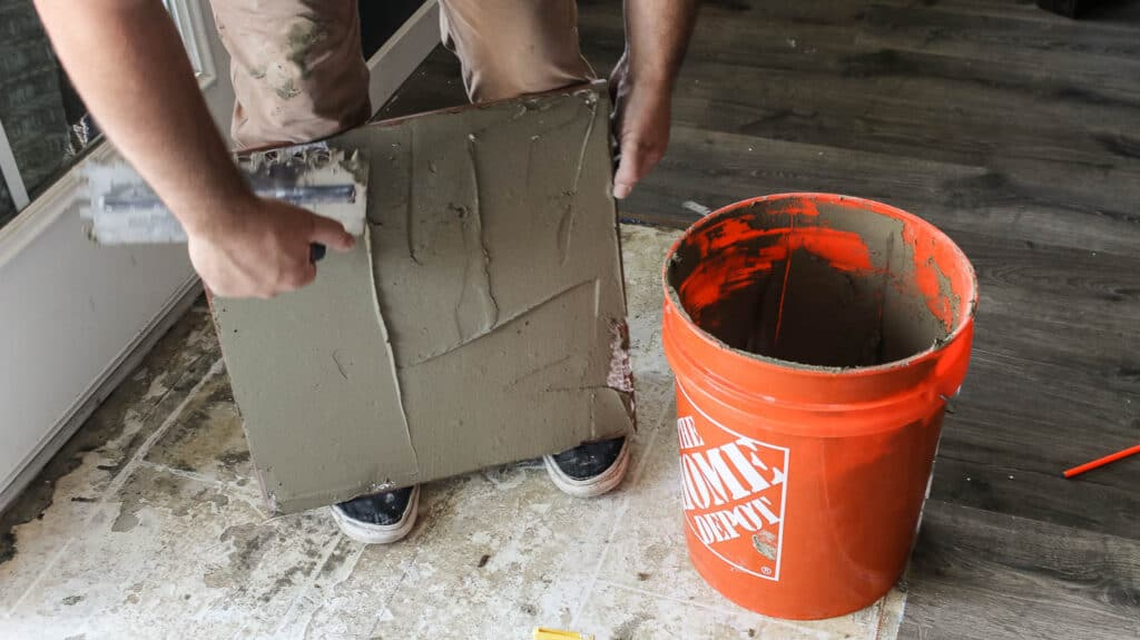 Before you set tiles into place, it is recommended that you back butter large format tiles by adding a thin layer of mortar to the back of the tile
