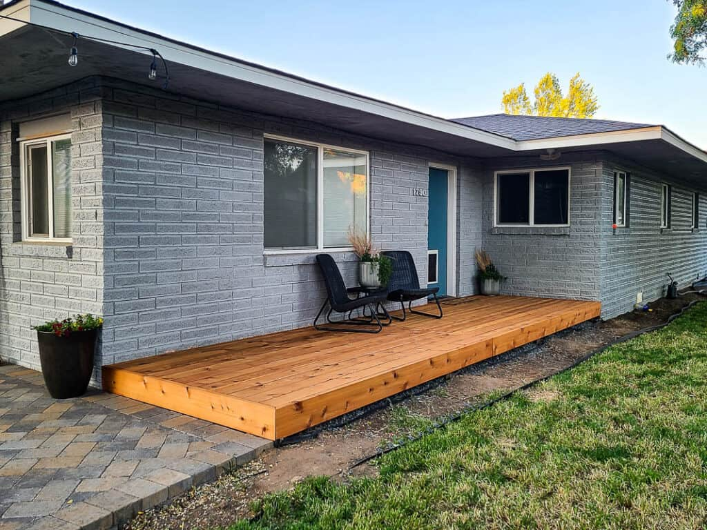 Full view of the backyard with wood deck board with two black chairs and center table with plants under the window and back door after the makeover