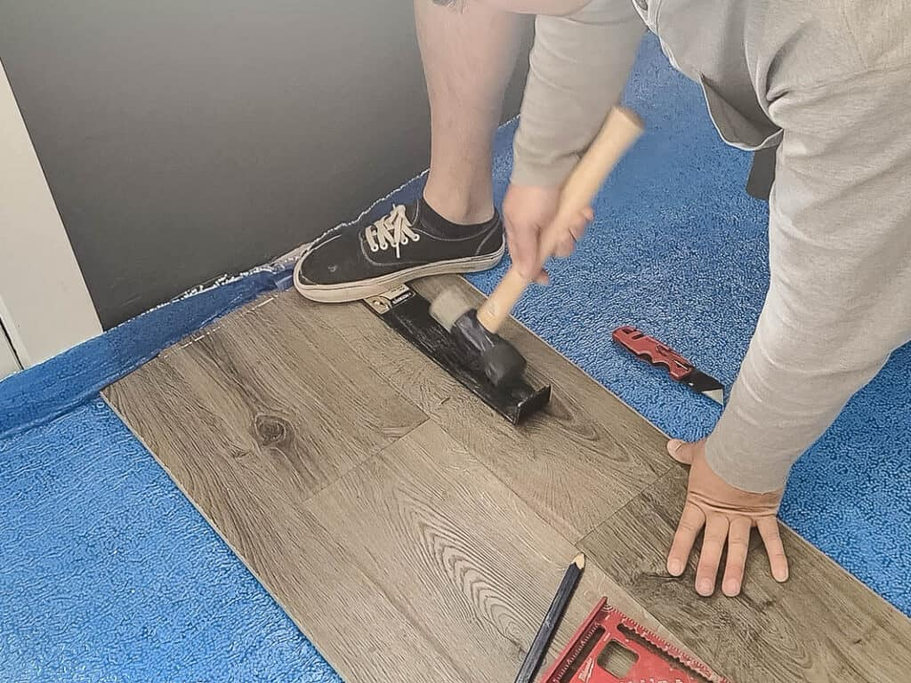 Man attaching the laminate flooring on the edge of the room with hammer and pull bar with other materials
