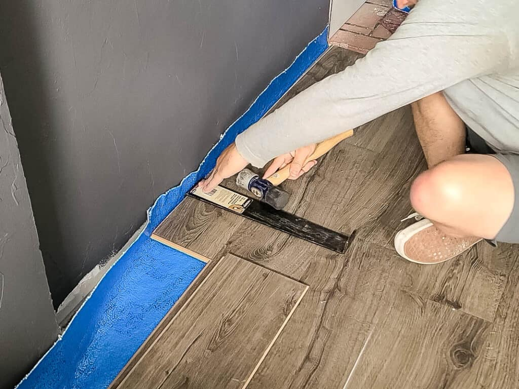Man sitting on the floor attaching the laminate floors along the edge of the room for the last row with hammer and pull bar