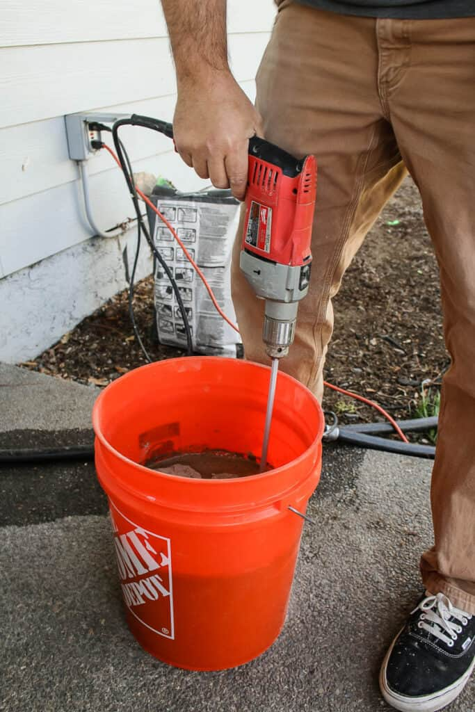 Man holding the drill to mix the thinset and water inside bucket before installing tile
